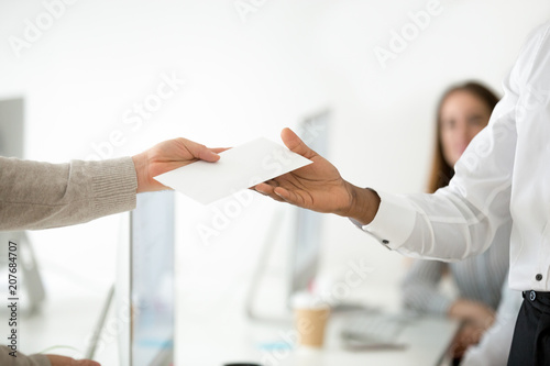 Fototapeta Close up of male CEO giving envelope to successful office worker with reward or money bonus for high work results, boss supporting motivating employee. Achievement, promotion, stimulation, HR concept obraz