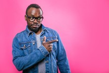 African Man In Glasses Pointing Finger To The Side On Pink Background