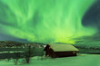 Leinwandbild Motiv Northern lights Aurora Borealis in the night above a typically artic style build house