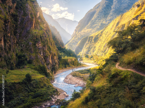 Fototapeta Colorful landscape with high Himalayan mountains, beautiful curving river, green forest, blue sky with clouds and yellow sunlight at sunset in summer in Nepal. Mountain valley. Travel in Himalayas obraz