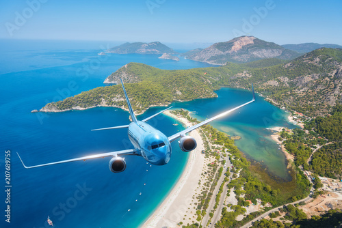 Türaufkleber Flugzeug Airplane is flying over islands and sea at sunrise in summer. Landscape with white passenger airplane, seashore, mountains, sky, and blue water. Blue passenger aircraft. Travel and resort. Tourism