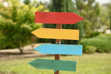 Empty Wooden Pointer, Four Colored Arrows With Copyspace On Background Of Summer Green Garden