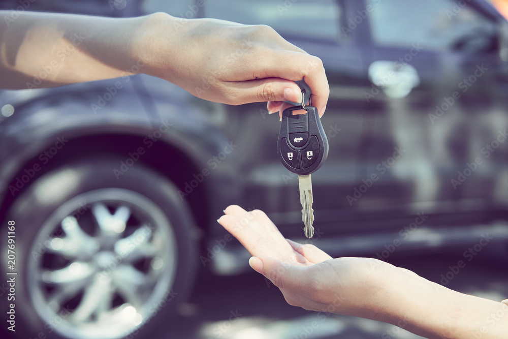 Fototapeta Woman's hand give the car key and blurred background.
