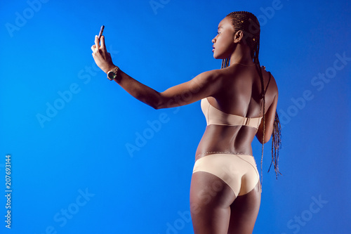 Foto op Plexiglas Akt The African model takes pictures of herself. Girl with African pigtails. Black photo model. A black girl is taking pictures of herself on the phone.
