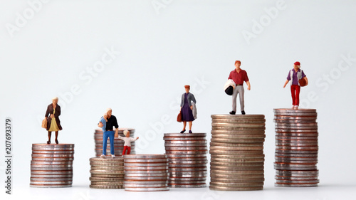 Fotografía  Miniature people standing on piles of different heights of coins