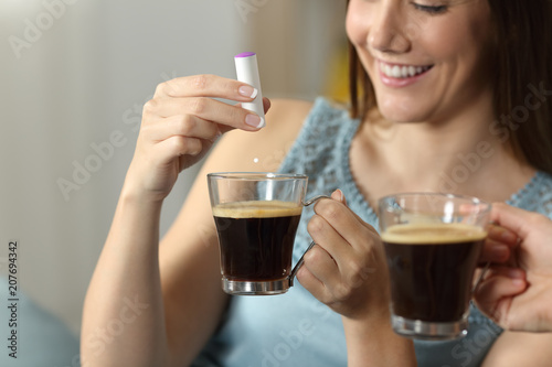 Woman hand throwing saccharine into a coffee cup Canvas Print