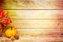 A Pumpkin With Pine Cones And Leaves With A Wood Background For Copy Space And Texture On The Edges.