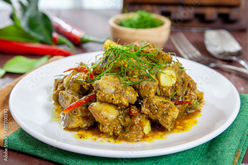Photo Fried pork bones spicy with yellow curry paste on dish thai style food