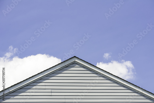 part of the roof and wall lined with white siding against the blue sky and white Tapéta, Fotótapéta