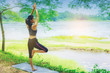 Young woman doing yoga pose under the tree close the nature