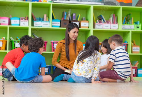 Asian female teacher teaching mixed race diversity group of kids reading book sitting on library floor in classroom,Kindergarten pre school concept Fotobehang