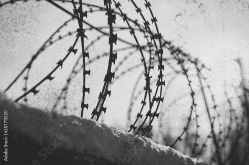 Photo  Barbed wire stretches along the concrete wall