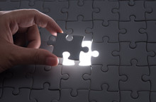 Hand Embed Missing Puzzle Piece Into Place With Light Glow,success, Teamwork And Finishing Or Ending