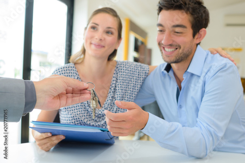 Papiers peints Individuel Estate agent handing keys to happy couple