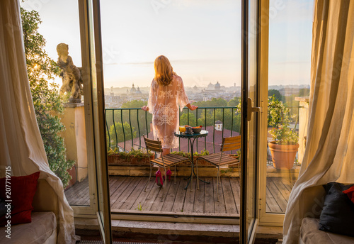 Fotografie, Obraz Woman standing on balcony and overlooking city at sunrise