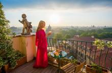 Woman Standing On Balcony With Glass Of Fresh Orange Juice