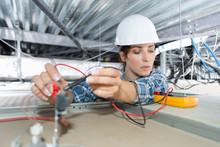 Female Electrician Working On ...