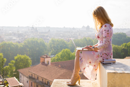 Fotografie, Obraz  Businesswoman working on laptop in early morning with city panorama in backgroun