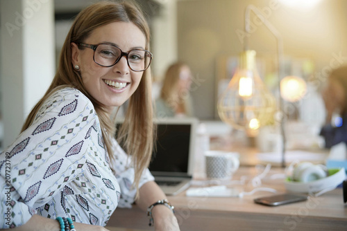 Papiers peints Individuel Cheerful trendy girl in co-working office