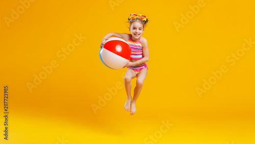 Obraz funny happy child  jumping in swimsuit    on colored background - fototapety do salonu