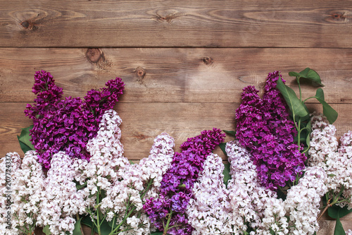 Photo sur Toile Lilac Bouquet of purple lilacs flowers on a brown wooden background