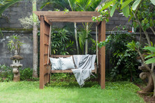 Classic Outdoor Wooden Swing In The Green Garden With Pillows And Blanket