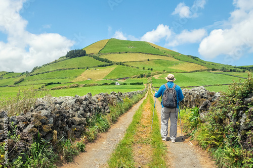 Foto auf Gartenposter Pistazie A man with a backpack and trekking poles walking along a country road, Sao Miguel island, Azores, Portugal