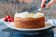 Woman Decorating Homemade Sour Cream Cake With Cream Cheese Frosting