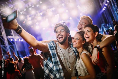Happy friends taking selfie at music festival - 207727914