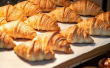 Croissants In A Bakery Shop. Freshly Baked Croissants On Texture Background.