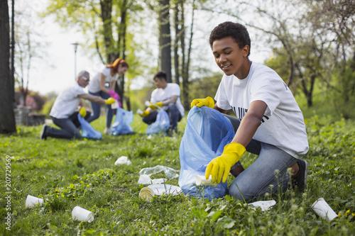 Wildlife volunteer. Energetic male volunteer using garbage bag while collecting litter