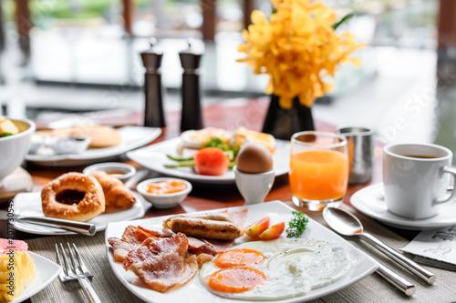 Fototapeta Setting of breakfast includes coffee, fresh orange juice, eggs on table in hotel restaurant obraz