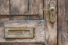 Close Up Detail Of An Old Wooden Door With Brass Handle An Mail Slot.