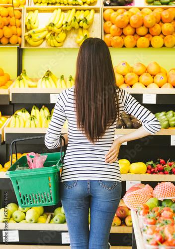 Plakat Tylny widok młoda kobieta w przypadkowych ubraniach z koszem dla jedzenia w ręce na tle owoc i warzywo w supermarkecie.
