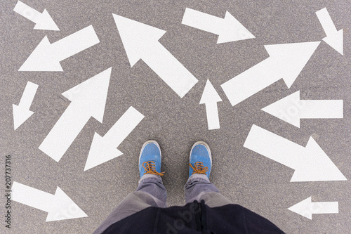 Obraz Confusing options direction arrows on asphalt ground, feet and shoes on floor - fototapety do salonu