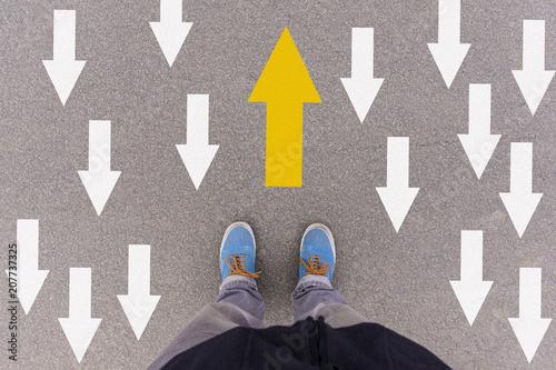 Photo direction arrows on asphalt ground, feet and shoes on floor