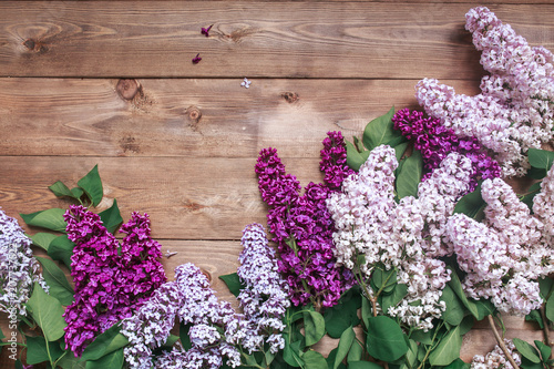 Foto op Aluminium Lilac Bouquet of purple lilacs flowers on a brown wooden background