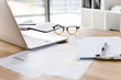 canvas print picture - Image of workplace in office room without people with open laptop, clipboard, glasses, pencil and notebook lying on wooden desk