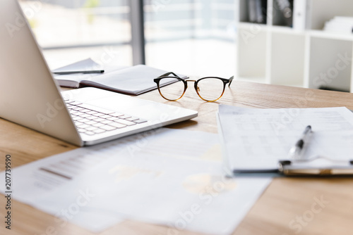 Image of workplace in office room without people with open laptop, clipboard, glasses, pencil and notebook lying on wooden desk