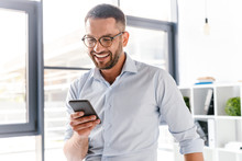 Image Closeup Of Smiling Employer Guy In White Shirt Standing In Office Room Near Big Window, And Using Smartphone For Work