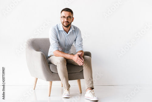 Fototapeta Horizontal portrait of attractive caucasian guy wearing stylish formal clothing sitting in armchair and looking at camera, isolated over white background obraz