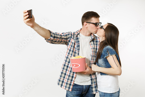 Photo  Young couple, woman and man in 3d glasses watching movie film on date, holding bucket of popcorn and cup of soda or cola, doing selfie on mobile phone isolated on white background