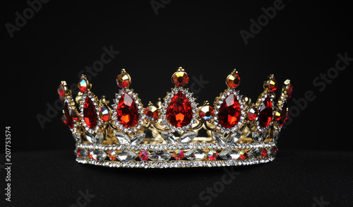 Valokuva  portrait of a beautiful jewelled ruby, diamond and golden crown, photographed on a black studio background
