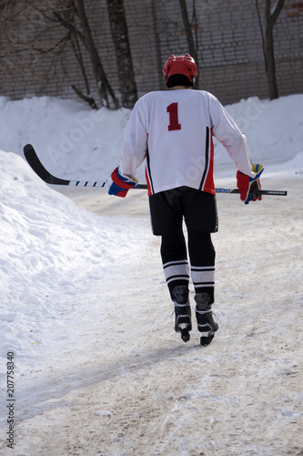 Ice hockey player in blue wear and green helmet . Canvas Print