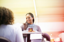 Woman At Check In Desk Holding Passport Smiling