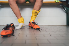 Football Player In One Football Boot In Changing Room