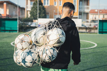 Football Player Carrying Net Of Balls On Pitch