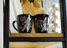 Two Black Cups With A Drawn Cat