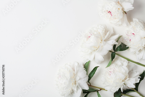Beautiful white peony flowers bouquet on pastel table top. Flat lay style.
