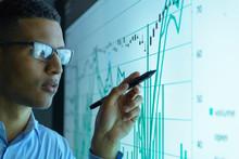 Businessman Studying Graphs On...